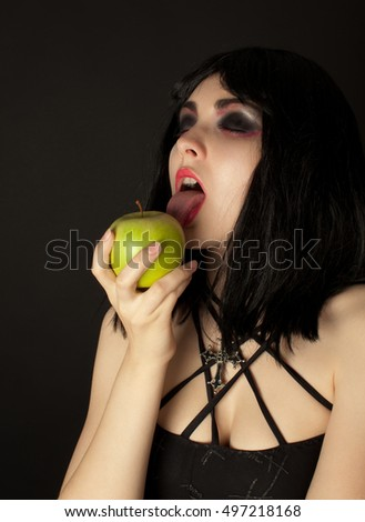 Picture of woman with halloweeen make up licking green apple