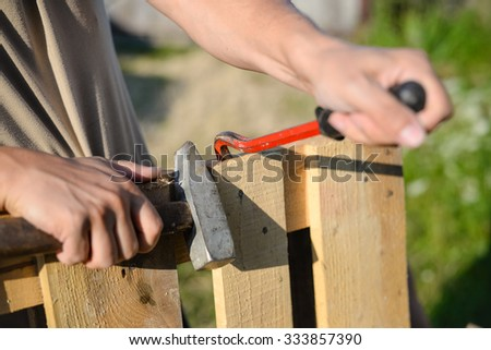 Picture of wood fence gate repairing. Closeup of male hands with crowbar and hammer on blurred summer outdoor background. - stock photo