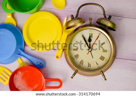 Picture of wooden tabletop with colorful toy dishware and vintage alarm clock. Plastic pates and cutlery with old clock on lilac plank background.
