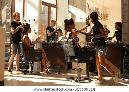 Picture of working day inside the beauty- sit on two chairs clients beautiful young girls. Hairdresser makes hair styling or hair cut, make-up artist doing make-up in a beauty salon- stock photo. - stock photo