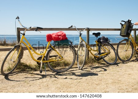 Picture of yellow bicycle with a picnic basket on - stock photo