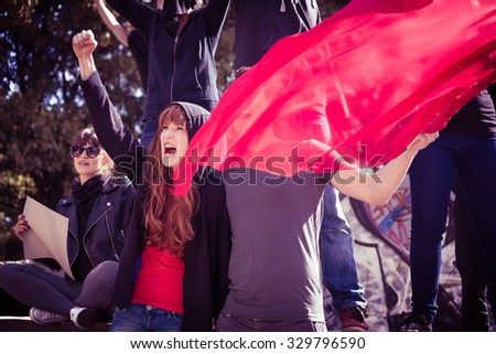 Picture of young active demonstrators with red flag - stock photo