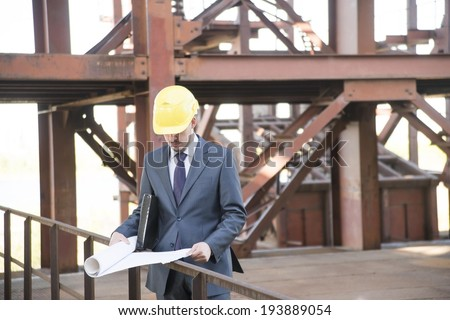 picture of young adult man engineer holding some blueprints and his hand in his pocket and looking at paper plan. on brown metal beam construction building background in perspective - stock photo