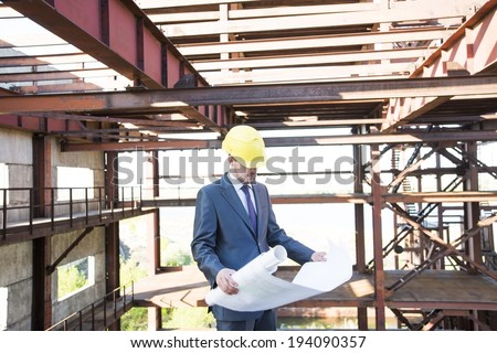 picture of young adult man engineer holding some blueprints and his hand in his pocket and looking at paper plan. on brown metal beam construction building background in perspective