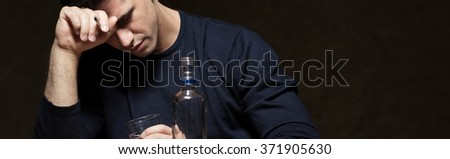 Picture of young broken man drinking alcohol - stock photo