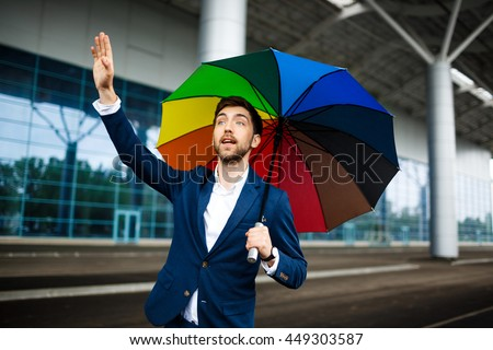 Picture of  young businessman holding motley umbrella catching car at station
