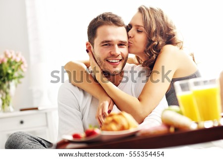 Picture of young couple eating breakfast in bed