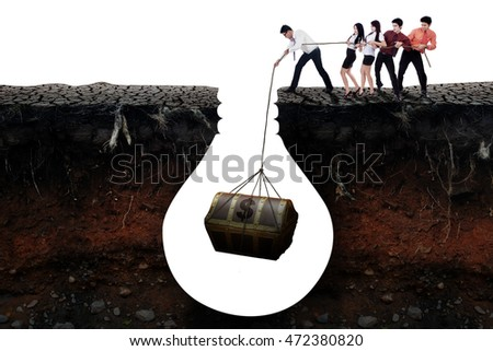 Picture of young entrepreneurs work together to get a treasure chest in the soil, isolated on white background