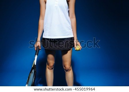 Picture of young fintess girl holding tennis racket and ball in studio - stock photo