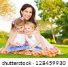Picture of young happy family, beautiful mother with two cute kids having fun outdoors in spring, pretty female with son and daughter sitting down on green meadow on backyard, daycare concept - stock photo