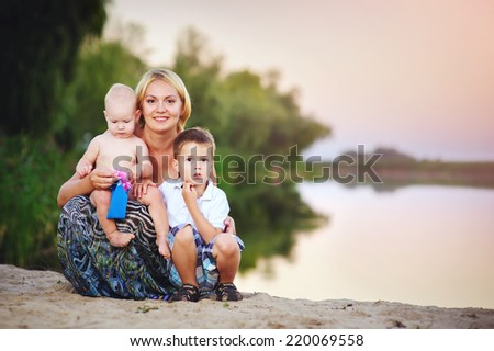 Picture of young mother hugging two little children, closeup portrait of happy family, cute blond female with daughter and son outdoor in spring time, smiling faces, happiness and love concept - stock photo