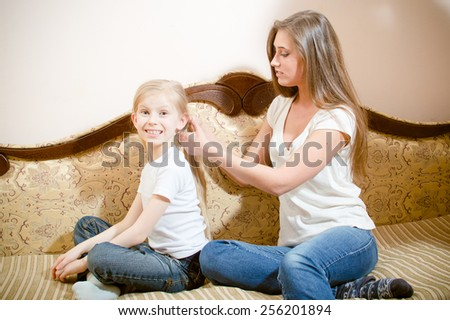 Picture of young pretty woman making hairstyle her girl child on sofa - stock photo