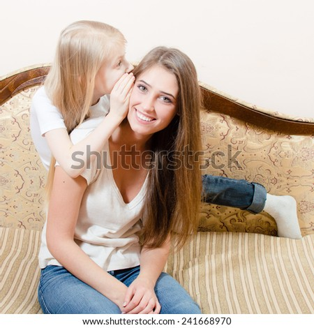 picture of young pretty woman sitting on a couch and the girl child whispers something in her ear - stock photo