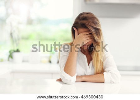 Picture of young sad woman in the kitchen