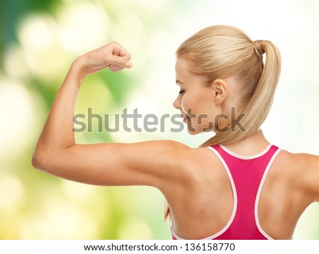 picture of young sporty woman showing her biceps - stock photo