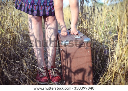 Picture of young woman and baby standing on retro suitcase barefoot in wheat field. Closeup of happy family resting on summer countryside background.