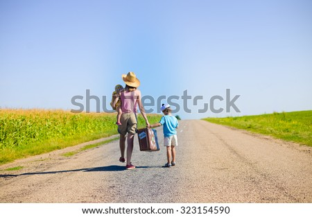 Picture of young woman carrying baby and suitcase walking away on road with little boy. Family travelling by foot on sunny summer countryside background. - stock photo