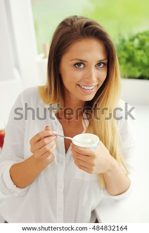 Picture of young woman with youghurt in the kitchen