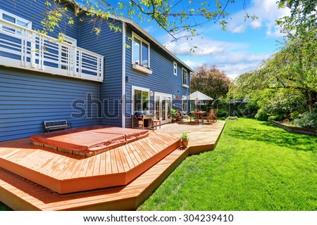 Picture perfect back deck with umbrella covered seats and lots of grass. - stock photo