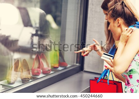 Picture presenting group of girlfriends shopping for shoes in the city with credit card - stock photo