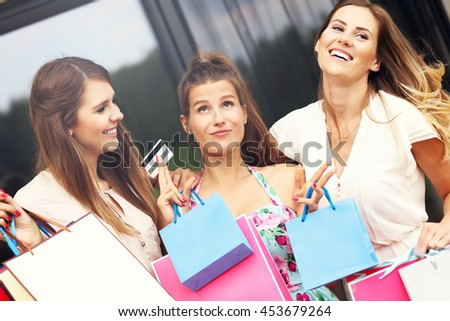 Picture presenting group of girlfriends shopping in the city with credit card