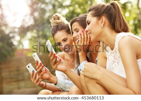 Picture presenting happy group of friends with smartphones sitting outdoors