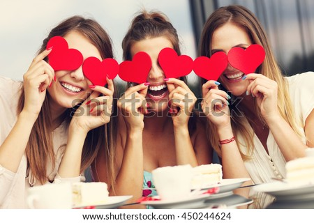 Picture presenting three girlfriends holding hearts in cafe - stock photo