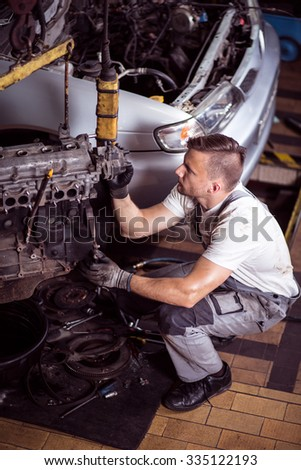 Picture showing mechanic operating lifting device for engine