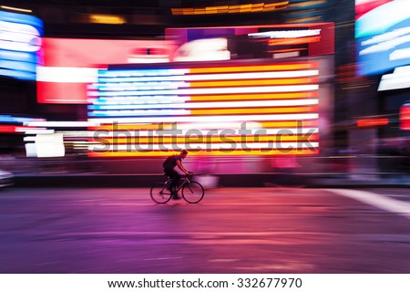 picture with camera made motion blur effect of a bicycle rider in front of US flag at Times Square, NYC - stock photo