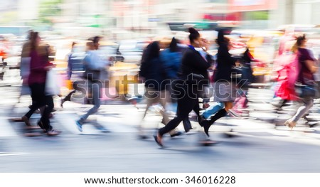 picture with camera made motion blur effect of a crowd of people crossing a city street