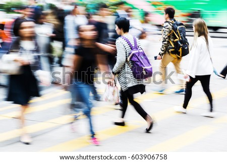 picture with motion blur of a crowd of people crossing a street