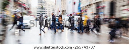 picture with zoom effect of a crowd of pedestrians crossing a street in the rainy city