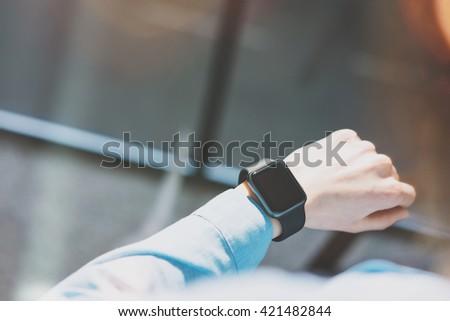 Picture Woman Working Modern Loft Studio.Girl Enjoying Generic Design Smart Watch.Looking Screen Smartwatch.Using Free Time Management. Horizontal mockup. Burred background. Film and bokeh effects. - stock photo