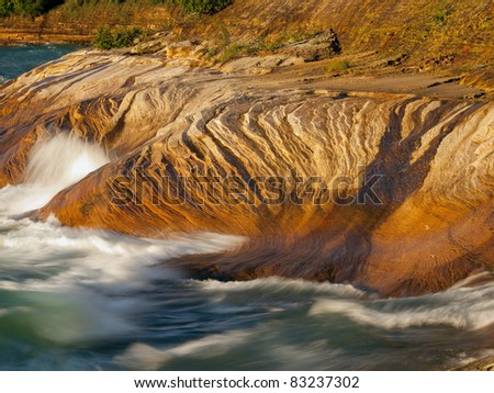 Pictured Rocks National Lakeshore in the Upper Peninsula of Michigan on the shore of Lake Superior at sunset. - stock photo