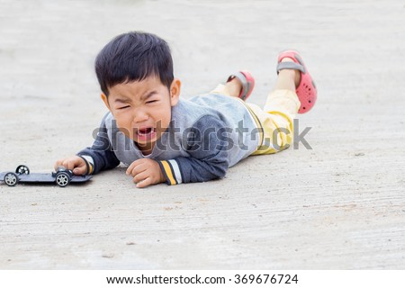 Pictures of Asian children crying on the sidewalk. - stock photo