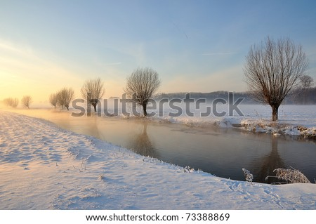 Picturesque and misty Dutch winter landscape with low sun, snow and partially ice on a narrow stream. Along the waterfront are bare willows. It is an award-winning photo of the municipality Drimmelen. - stock photo