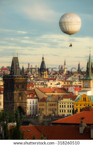 Picturesque and romantic view over the oldtown and the charles bridge of Prague having a balloon in the late afternoon sky. Soft colors. - stock photo