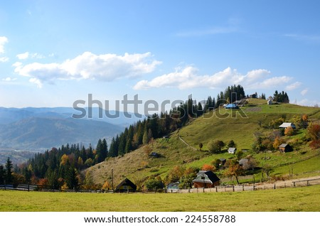 Picturesque autumn rural landscape on a background of blue sky with clouds in Carpathian mountains, Ukraine