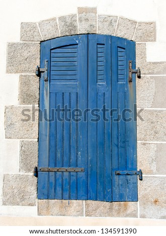 Picturesque Britton window with blue shutters