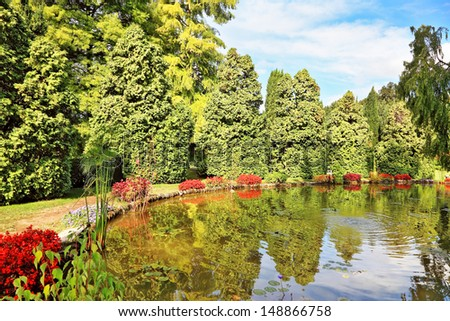 Picturesque bush with red flowers around a circular pond. Beautiful park in northern Italy - Sigurta - stock photo