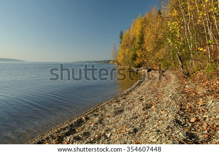 Picturesque, colorful autumn landscape, river, forest, hill, blue sky with clouds.
