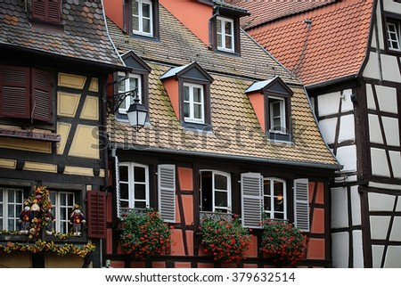 Picturesque half-timbered old french facades with flowers and shutters on windows in Colmar, horizontal photo