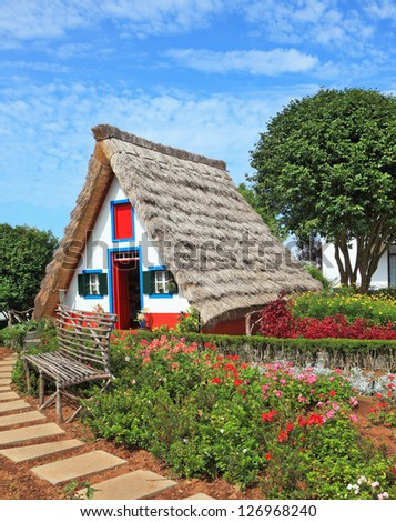 Picturesque house-museum of the first colonists to Madeira. Charming white cottage with a thatched roof and gable small garden with flowers - stock photo