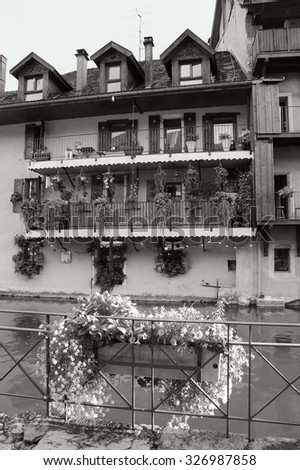 Picturesque houses over the canal in old town of Annecy (France) at sunset. Aged photo. black and white. - stock photo
