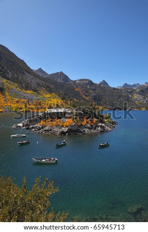 Picturesque island on mountain lake. Fishing boats are moored about island