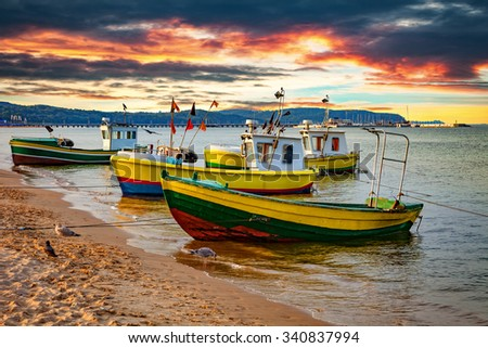 Picturesque landscape of a sunset with a boats on beach in Sopot, Poland. - stock photo