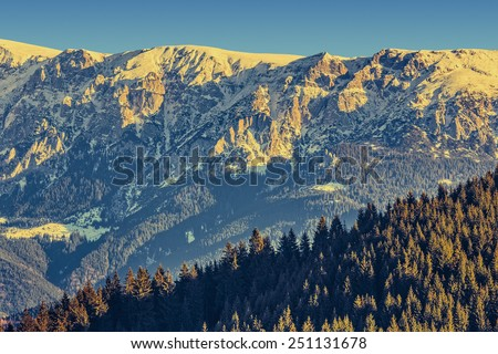 Picturesque landscape of sunlit Bucegi mountains ridge with steep slopes covered by snow at sunrise, Romania. - stock photo