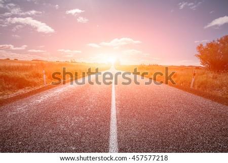 Picturesque landscape scene and sunrise above road - stock photo