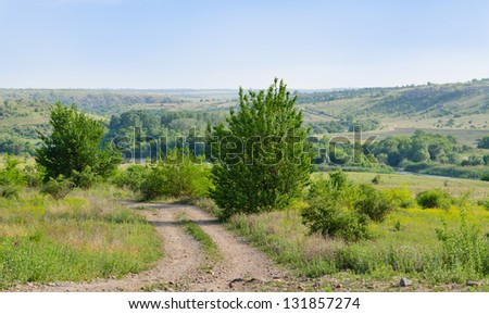 Picturesque landscape view of a deserted rural dirt track or farm lane leading into a green valley between gently rolling hills - stock photo