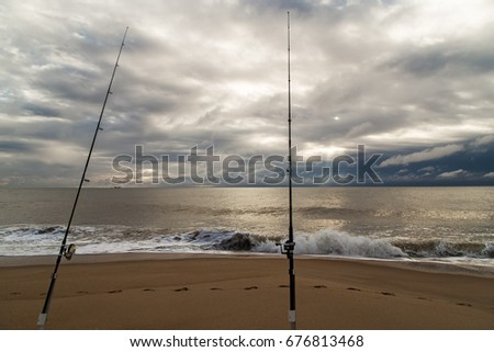 Picturesque landscape with fishing rods on the sandy beach on Atlantic ocean coast,dramatic clouds as background,NC,USA